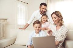 Семья при 2 прелестных дет сидя совместно и используя компьтер-книжку дома Стоковое фото RF