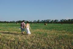 Семья при ребенок идя на поле Стоковые Фото