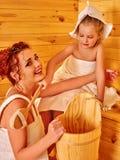 Семья при ребенок ослабляя на сауне Стоковые Изображения