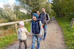 Семья при рюкзаки или идя в древесины стоковые изображения