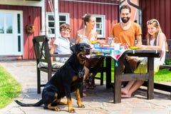 Семья при собака есть в фронте сада дома стоковые фото