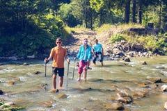 Семья путешественников пересекает реку горы стоковая фотография