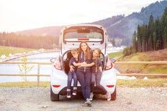Семья путешествуя автомобилем и имея потеху на автостоянке Стоковое Фото