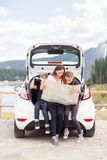 Семья путешествуя автомобилем и используя карту для того чтобы проводить Стоковые Фотографии RF