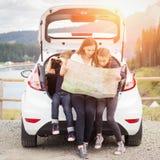 Семья путешествуя автомобилем и используя карту для того чтобы проводить Стоковые Изображения
