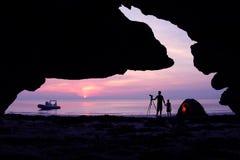 Семья располагаясь лагерем на пляже перед пещерой с частной шлюпкой Стоковое фото RF
