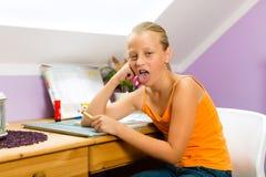 Семья - ребенок делая домашнюю работу стоковая фотография