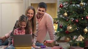 Семья рождества беседуя на интернете с компьтер-книжкой сток-видео