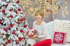 Семья рождества совместно cellebrating дочь и мать Нового Года праздника близко к белому дереву xmas с снегом и красными игрушкам Стоковые Изображения