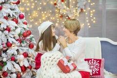 Семья рождества совместно cellebrating дочь и мать Нового Года праздника близко к белому дереву xmas с снегом и красными игрушкам Стоковое Изображение RF