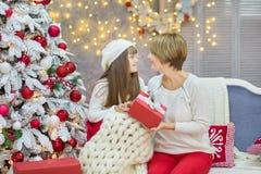 Семья рождества совместно cellebrating дочь и мать Нового Года праздника близко к белому дереву xmas с снегом и красными игрушкам Стоковые Фото