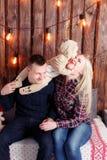 семья рождества счастливая Родители и усаживание младенца стена деревянных планок и гирлянды Стоковое Изображение RF