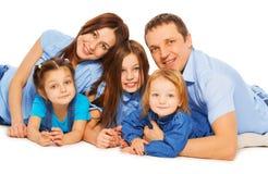 Семья родителей и 3 девушек лежа на поле стоковое фото