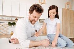 Семья родитель-одиночки тратя время совместно пока делающ головоломку стоковое фото