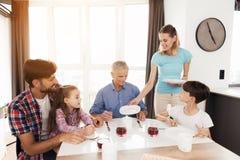 Семья сидит на обеденном столе Женщина аранжирует плиты перед ими Стоковые Фото