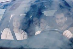Семья сидя в автомобиле смотря вне окна стоковое изображение