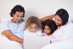 Семья сидя на кровати занимаясь серфингом интернет Стоковое Изображение