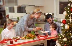 Семья сидя на таблице наслаждаясь едой рождества Стоковые Фото