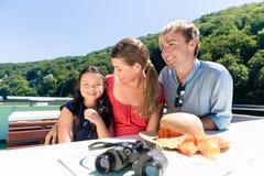 Семья сидя счастливо на шлюпке на круизе реки в лете Стоковые Изображения RF