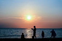 Семья силуэта смотря заход солнца на заходе солнца пляжа Стоковые Фотографии RF