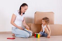 Семья сидит в комнате около коробок Стоковое Фото