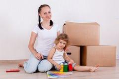Семья сидит в комнате около коробок Стоковое Изображение RF