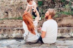 Семья сидит на речном береге Стоковые Фотографии RF