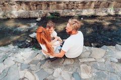 Семья сидит на речном береге Стоковые Изображения RF