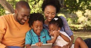 Семья сидит на траве и смотрит таблетку видеоматериал