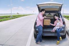 Семья сидя в автомобиле с корзиной пикника стоковое изображение
