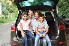 Семья сидя в багажнике автомобиля готовом для того чтобы пойти стоковые фотографии rf