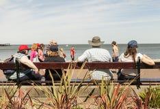 Семья сидя на длинном деревянном общественном стенде смотря вне к морю Стоковое фото RF