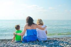 Семья сидя на каменном пляже Стоковая Фотография