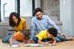 Семья сидя на ковре в живущей комнате Стоковое Изображение RF