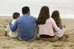 Семья сидя на пляже Стоковая Фотография