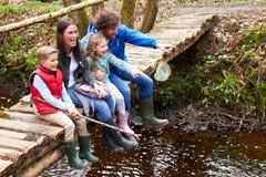 Семья сидя на рыбной ловле моста в пруде с сетью стоковое изображение