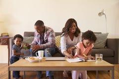 Семья сидя на софе как цвета дочери в книжке с картинками Стоковые Изображения RF