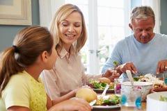 Семья сидя на таблице наслаждаясь едой дома совместно Стоковые Фотографии RF