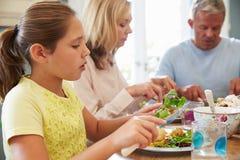 Семья сидя на таблице наслаждаясь едой дома совместно Стоковые Фото