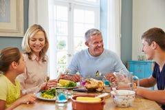 Семья сидя на таблице наслаждаясь едой дома совместно Стоковое Фото