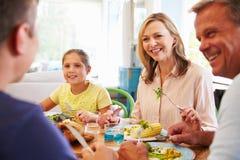 Семья сидя на таблице наслаждаясь едой дома совместно Стоковые Изображения RF