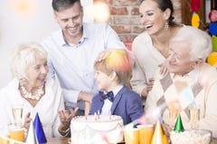 Семья сидя около именниного пирога стоковые изображения