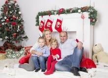 Семья сидя около камина рождества Стоковое Фото