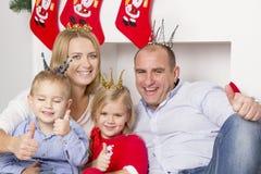 Семья сидя около камина рождества Стоковая Фотография RF