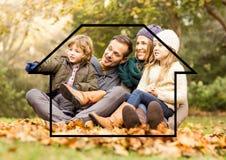 Семья сидя outdoors против плана дома в предпосылке Стоковое фото RF