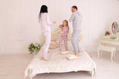Семья скача и околпачивая вокруг в кровати, супруг и жена воюют Стоковые Фотографии RF