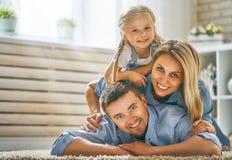 Семья смеясь над и обнимая стоковое фото
