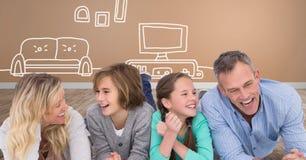 Семья смеясь над совместно имеющ потеху с чертежами дома и телевидения Стоковое Фото