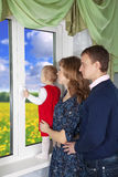 Семья смотря вне окно Стоковые Изображения RF