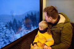 Семья смотря из окна поезда во время перемещения на железной дороге cogwheel/железной дороге шкафа в горах Альпов стоковое изображение